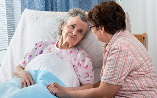 Пожилая женщина лежит в кровати