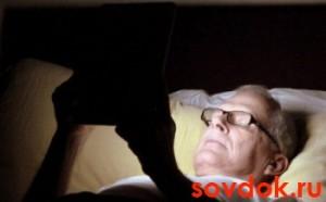 Мужчина в кровати с планшетом