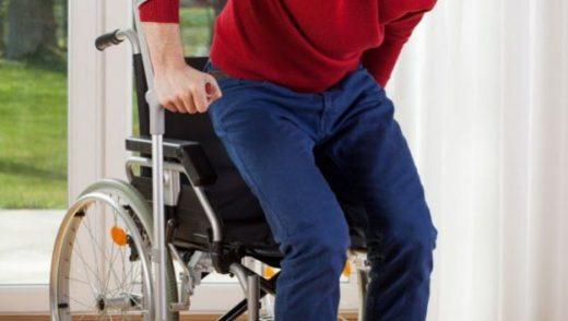 Человек встаёт с инвалидного кресла