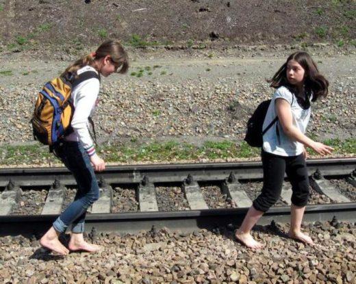 Девочки идут босиком по камням