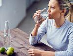 девушка сидит за столом и пьёт воду