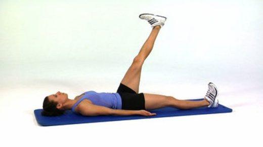 Девушка выполняет упражнение — подъем ног лёжа на спине