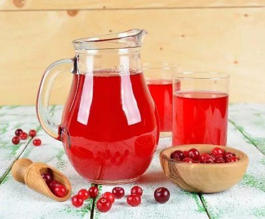 Клюквенный морс в графине и стаканах и ягоды клюквы на столе и в чашке