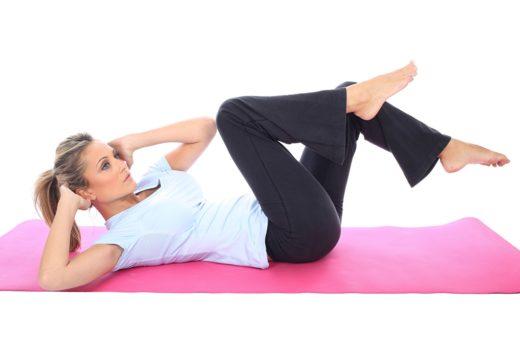 Девушка выполняет упражнение, лёжа на спине