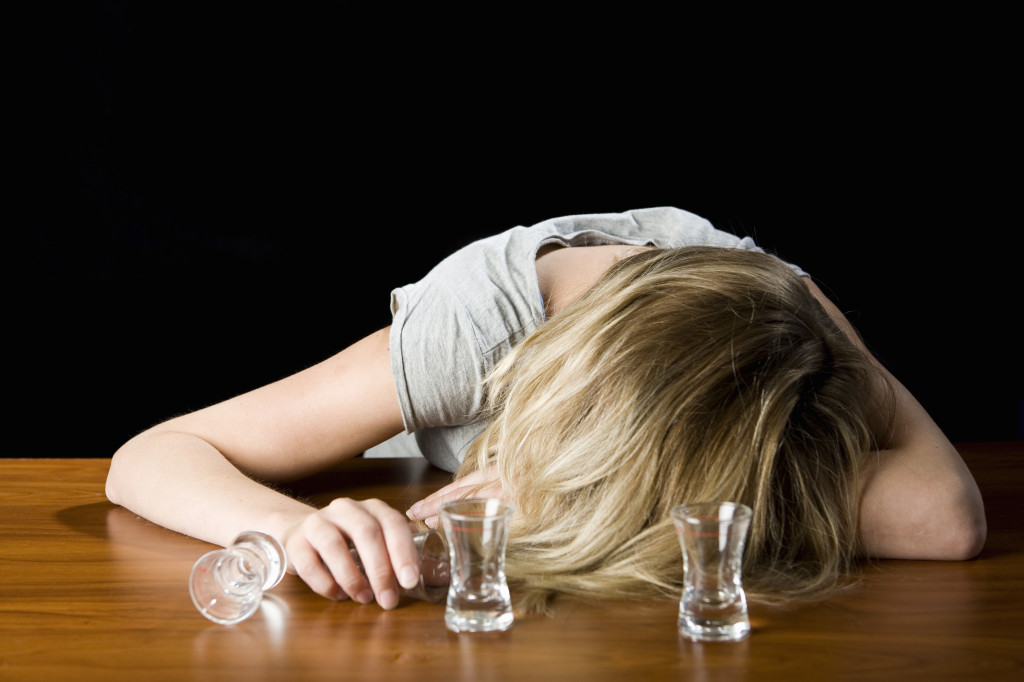 A Young Woman Passed Out Drunk on a Bar Counter