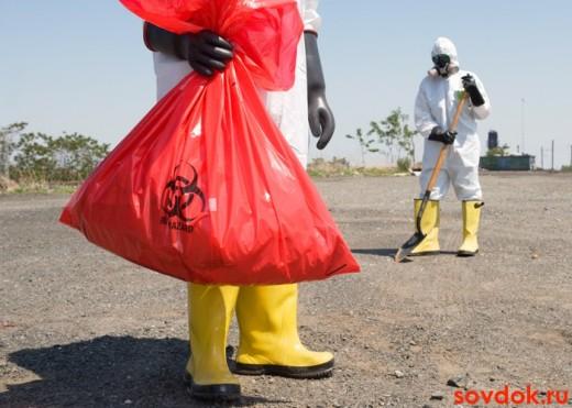 люди в костюмах собирают токсические отходы