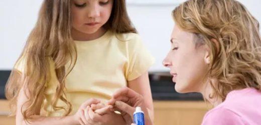 Мама обрабатывает рану от извлечения занозы у дочки