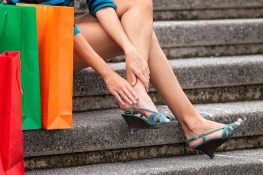 Девушка в босоножках сидит на ступеньках