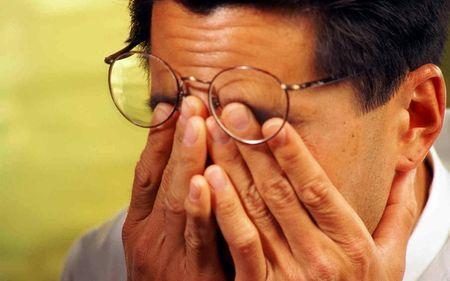 Мужчина в очках трёт глаза
