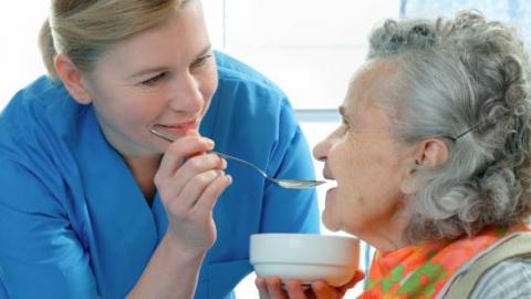Медсества кормит пожилую женщину