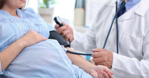 Врач измеряет давление у беременной