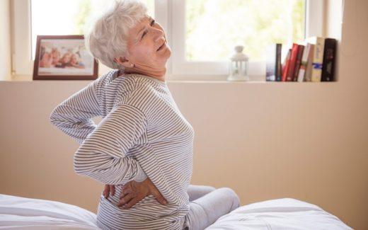 пожилая женщина на кровати держится за поясницу