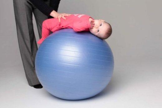 Ребёнок на фитболе животом вверх