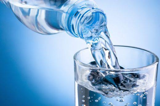 Процесс наливания воды из бутылки в стакан