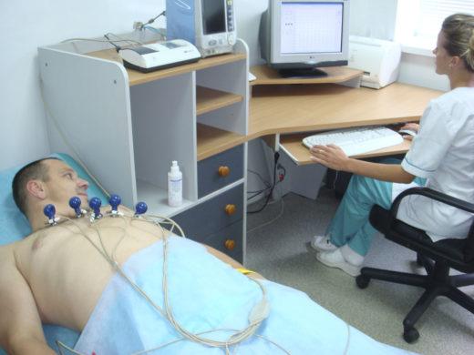 Врач делает ЭКГ пациенту
