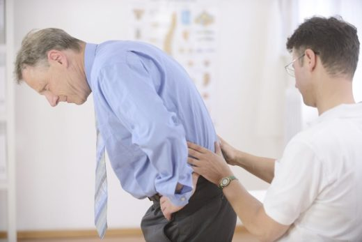Врач осматривает поясницу пациента