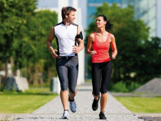 Мужчина и женщина бегут по дорожке в парке