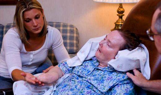 Женщина держит за руку больную хореей Гентингтона
