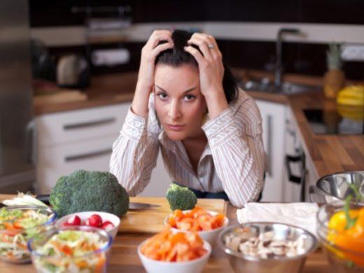 Женщина за столом, уставленным чашками с овощами