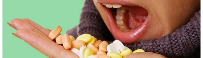 женщина держит в руке гору таблеток